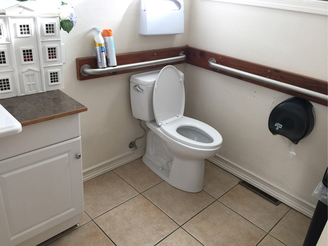 Bathroom showing hand rails around toilet and room to turn around in